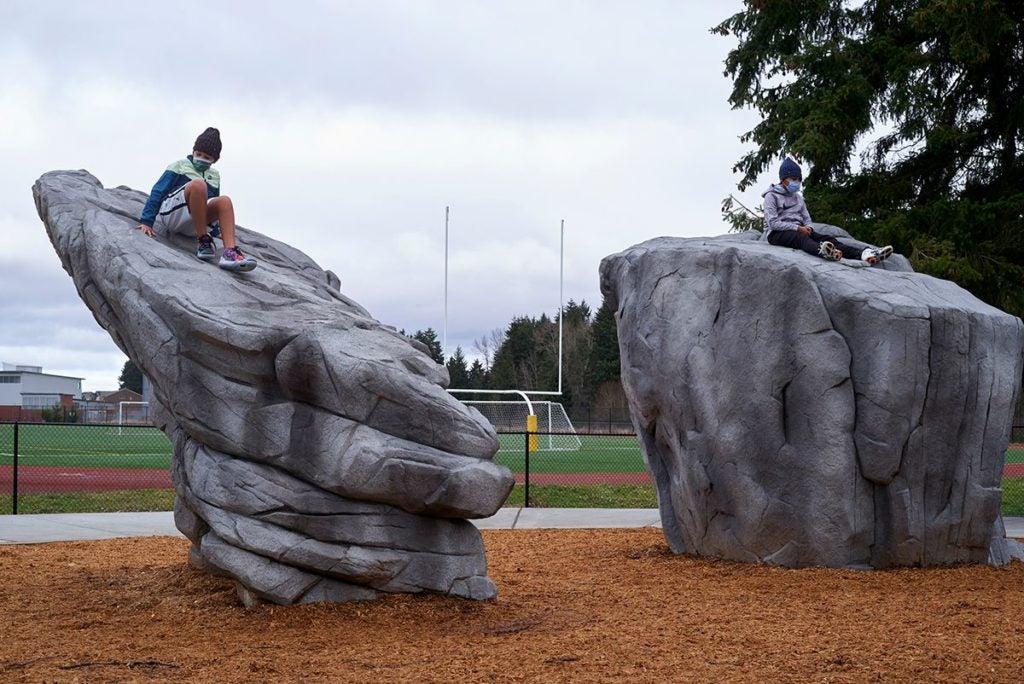 teenagers climbing boulders