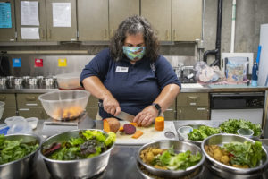 keeper Monica chopping veggies
