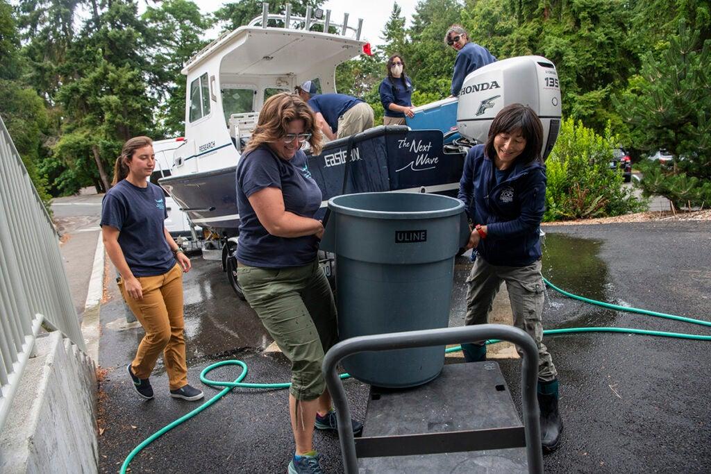 aquarists unload and hose the boat